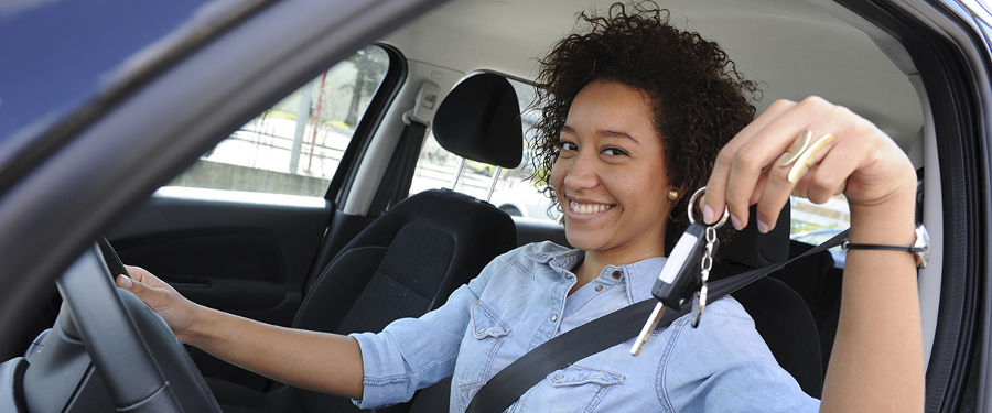 woman in car showing keys